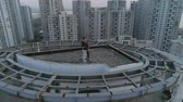 魂 : Aerial orbital shot of couple in love standing on the roof top of modern apartments building and enjoying the sunset