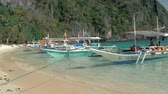 indigeni : El Nido, Philippines - February 1, 2019: Close-up shot of traditional filipino bangka boats anchored on gorgeous tropical beach. Travel concept. Palawan island, Philippines. Filmati Stock