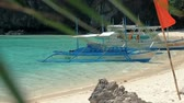 indigeni : El Nido, Philippines - February 1, 2019: Traditional filipino bangka boats anchored on gorgeous tropical beach. Travel concept. Palawan island, Philippines.