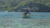 indigeni : El Nido, Philippines - February 4, 2019: Traditional filipino bangka boats anchored on gorgeous tropical beach. Travel concept. Palawan island, Philippines. Filmati Stock