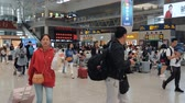 várakozás : Shanghai, China - May 11, 2019: Hongqiao railway station departures area passenger crowds. Many people walking to gates to board high speed trains in Chinese modern train station in daytime. Stock mozgókép