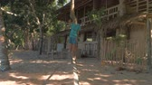 algarve : El Nido, Philippines - February 8, 2019: Slow motion shot of young philippines boy goes backwards and balance on slackline on the beach Stock Footage