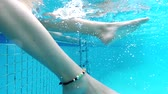 stopy : Underwater view of tender woman splashing water with her feet. Joy of hot summer day. Swimming pool and sunshine. Slow motion shot.