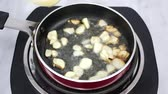 fokhagyma : Video of sliced garlic quickly browning in olive oil while being stirred on an electric one burner stovetop.