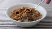 даты : A bowl of pecans, raisins and dates breakfast cereal with skim milk on a striped table cloth being carefully eaten.