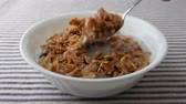 lanche : A bowl of pecans, raisins and dates breakfast cereal with skim milk on a striped table cloth being eaten.