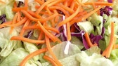 saláta : Close video of dropping sliced carrots onto a fresh salad.