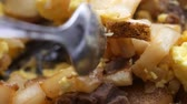 бифштекс : Close video of a breakfast meal on a plate with eggs, potatoes, cheese and steak being stirred with a spoon.