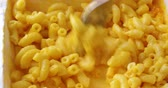queijo cheddar : Video of macaroni and cheese in a microwavable paper tray being briskly stirred with a fork after heating. Vídeos