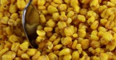 ropogós : Close video of stirring toasted corn nuts with a spoon then taking one spoonful. Stock mozgókép