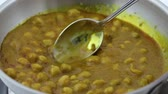 отопление : Video of a white chickpeas Indian curry meal being slowly stirred in a skillet. Стоковые видеозаписи