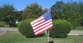 póly : A small American flag waving in the wind in a well kept cemetery.