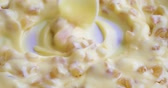 Video of stirring dried diced peach chunks into creamy banana cream pudding then taking a spoonful at the end.