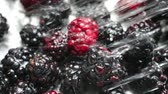 Close slow motion video of ripe blackberries being rinsed with water in a stainless steel colander.
