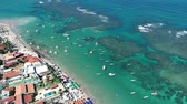 Aerial view of Porto de Galinhas Beach, Pernambuco, Brazil: unique experience of swimming with fish in natural pools. Fantastic vacation travel. Candles, sailboats, rafts, boats in the harbor!