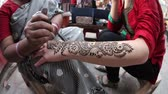 hlavní : NEW DELHI, INDIA - FEBUARY 23, 2015: Indian woman making henna painting on tourist hand at Main bazaar street in Paharganj