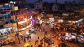 pobreza : New Delhi, INDIA -  JANUARY 21, 2015: Night view of Main bazar Pahar Ganj street in New Delhi. People, cars, motorbikes and auto rickshaws on the street near by shops at night