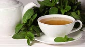 byliny : Woman add sugar cubes into the Cup tea with mint