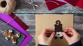 natal : Woman making monkey Christmas toy from felt at wooden background