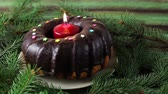 Christmas cake with burning candle naer pine tree decorative branches.Close up shot.