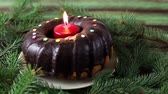 Christmas cake with burning candle near pine tree decorative branches.Close up shot.