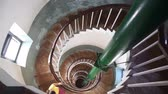 Woman going down by spiral stairs inside of lighthouse in Kovalam, Kerala, India Stock Footage