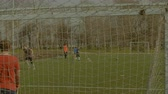 quatro pessoas : Young striker taking a shot on goal and soccer ball blazing out the goals crossbar during football training session on sports field. Soccer player shooting on goal and missing on football pitch.