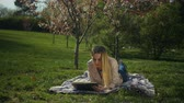 keménytáblás : Charming blonde young woman enjoying leisure in blooming spring park reading a book while lying on blanket on park lawn. Intelligent female student studying with book in spring park. Slow motion.