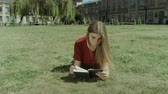 conta : Beautiful smart long brown hair girl reading a book while lying on campus green lawn. Charming intelligent young woman enjoying leisure reading interesting book on park lawn. Low angle view.