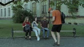 cronometragem : Group of college friends rushing to lecture in university campus. Concerned male student pointing the time on the watch to his classmates and university students hurry up to study. Stabilized shot. Stock Footage