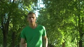 maratona : Portrait of handsome active healthy runner jogging in summer park over beautiful landscape background. Closeup. Sporty male jogger running in public park during outdoor workout. Slow motion. Stock Footage