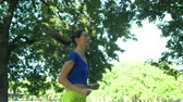 марафон : Charming long brown hair fit woman with ponytail in sporswear running in summer park over colorful landscape background. Sporty female runner jogging on path in public park. Slow motion.