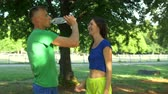 hidratáció : Sporty fit man crossing the finish line and refreshing himself with cold water after running in park. Smiling fit woman giving bottle of water to male jogger after run. Stabilized shot. slow motion.
