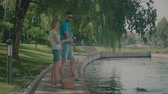 heteroszexuális párok : Attractive millennial married couple standing by the pond and feeding ducks while relaxing together in summer park. Positive couple enjoying leisure in nature. Slow motion.