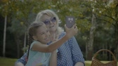 unoka : Cute smiling granddaughter taking a selfie on smart phone with joyful senior grandmother in the park. Happy preteen girl and cheerful grandmother making self portrait on cellphone in nature.