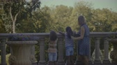 korkuluk : Rear view of milti ethnic family with two little mixed race girls admiring scenic view in travel location while leaning on stone railing during summer vacations. Happy diverse family on their vacation Stok Video