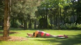 omurga : Lovely active woman in sports clothing doing stretching, warming up exercises for leg muscles, arms and spine in summer park while sitting on exercise mat during workout in nature. Slow motion.