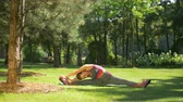 lábtörlő : Healthy lifestyle sporty woman exercising and stretching her body while sitting on exercise mat in summer park. Active female doing warming up exercises for leg muscles, arms and spine outdoors. Stock mozgókép