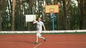 tenisz : Amateur male tennis player approching a forehand volley near the net to score a point during tennis match on hardcourt. Active sporty man playing tennis and hitting volley shot in vicinity of the net.