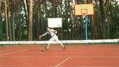 alcançando : Sporty male tennis player running to reach a tennis ball on hardcourt during tennis match. Active fit man missing a shot and losing a point while playing game on outdoor court. Slow motion.
