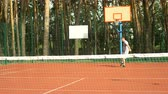 bodování : Attractive active sporty man playing tennis on hardcourt during training session. Amateur tennis player hitting tennis ball with forehand grip technique to score a point during tennis match outdoors.