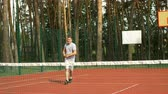 bodování : Cheerful sporty male tennis player scoring a matchpoint and winning tennis game on hardcourt. Two men in sports clothing shaking hands while standing near the tennis net on court after match. Slo mo. Dostupné videozáznamy