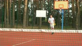 skóre : Active healhty lifstyle millennial man in sports clothing playing tennis game on hardcourt. Positive amateur tennis player hitting ball with different grip techniques during training session outdoors.