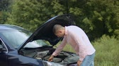 beira da estrada : Worried handsome male driver standing near broken car with opened bonnet and looking under hood outdoors. Man checking the car engine oil looking at dipstick after breakdown during road trip. Stock Footage