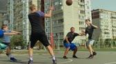 chránit : Sporty teenage streetball defending player jumping to block shot from offensive player on court during basketball game. Young male basketball player blocking shot attempt of opponent outdoors. Slo mo.