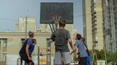 abroncs : Rear view of sporty teenager basketball player taking a free throw and scoring point while playing streetball game on basketball court on street. Streetball man shooting a free throw after foul.