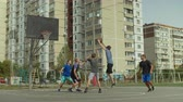 дриблинг : Sporty teenage streetball player making successful assist to teammate while playing game on basketball court. Basketball player passing ball and teammate scoring field goals during streetball match.