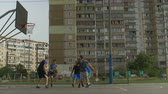 abroncs : Sporty teenage basketball players playing streetball game on basketball court over cityscape background. Side view. Streetball player failing to score field goal after assist during basketball game.