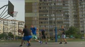 drible : Teenage streetball player dribbling and passing ball to teammate while playing basketball game on street court. Male basketball player taking two point shot and failed to score during streetball match Stock Footage