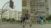 skóre : Offensive streetball team making chest pass and scoring field goal while playing basketball game on outdoor court. Teenage streeball players passing the ball and scoring points during basketball match